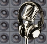 professional ''retro'' microphone & dj headphones against the wall of speakers