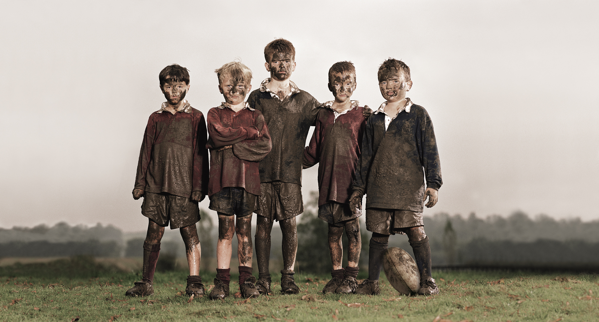 Five boys (8-10) with footall, covered in mud, portrait